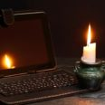 49927316 - blackout concept. lighting candle near laptop with dark empty screen
